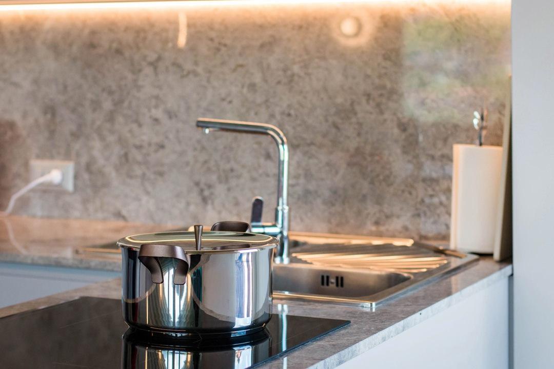 dettagli-piano-cottura-induzione-cucina-piano-marmo-venato-illuminazione-sottopensile